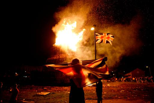 A boy holds a Union Jack flag in front of a bonfire in the Shankill Road area ahead of last year's July 12 celebrations by members of the Orange Order in Belfast. Photo: Reuters