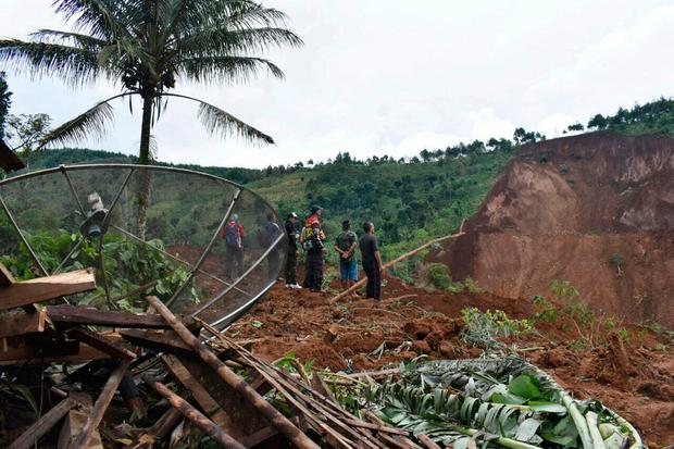 Rescuers search for victims in a neighborhood hit by a landslide in the village of Banaran, Ponorogo, East Java, Indonesia (AP Photo/Firdaus)