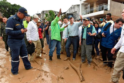 Colombia's President Juan Manuel Santos (4th R) gestures while visiting a flooded area Cesar Carrion/Colombian Presidency/Handout via Reuters