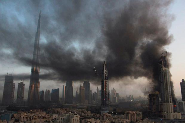 Smoke rises from a fire at a construction site next to Dubai Mall in Dubai, United Arab Emirates, Sunday, April 2, 2017. A large fire broke out early Sunday at a construction site near Dubais largest shopping mall, sending thick gray smoke billowing over the heart of the city. (Anthea Ayache via AP)