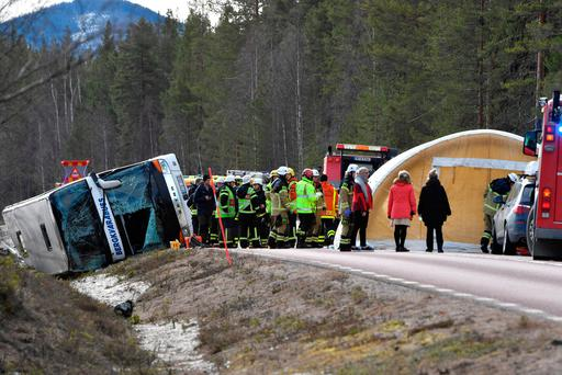 Rescue workers are seen at the site where a bus carrying school children and adults rolled over on a road close to the town of Sveg, in northern Sweden. (Reuters)