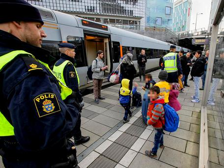 Police stand with refugee children in Sweden. The country has for years experienced the unique phenomenon of 'resignation syndrome' Getty