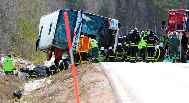 Rescue workers are seen at the site where a bus carrying school children and adults rolled over on a road close to the town of Sveg, in northern Sweden April 2, 2017. TT News Agency/Nisse Schmidt/via REUTERS