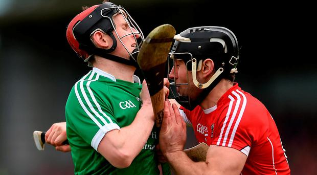 David Dempsey of Limerick is tackled by Cork's Mark Ellis at Páirc Uí Rinn yesterday. Photo: Eóin Noonan/Sportsfile