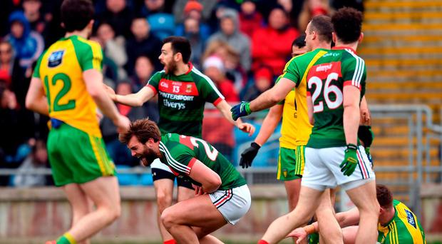Mayo's Aidan O'Shea falls to the ground in the incident which saw Donegal's Eamonn Doherty (right) sent off at MacHale Park. Photo: Stephen McCarthy/Sportsfile