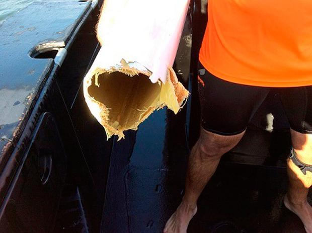 A 39-year-old man stands on his damaged kayak after an attack by a shark in Moreton Bay off Brisbane, Australia. (Queensland Police Service via AP)