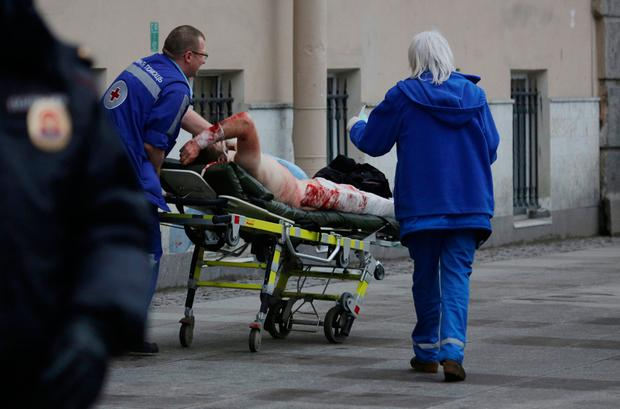 An injured person is helped by emergency services outside Sennaya Ploshchad metro station, following explosions in two train carriages at metro stations in St. Petersburg, Russia April 3, 2017. REUTERS/Anton Vaganov