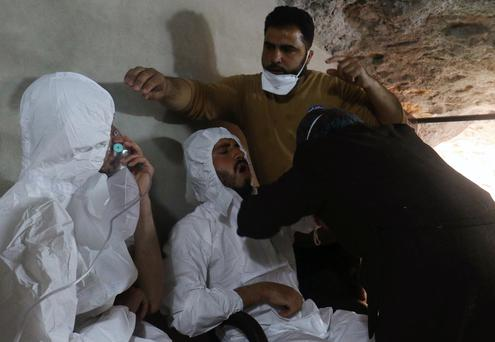 A man breathes through an oxygen mask as another one receives treatments, after what rescue workers described as a suspected gas attack in the town of Khan Sheikhoun in rebel-held Idlib, Syria Photo: Reuters/Ammar Abdullah