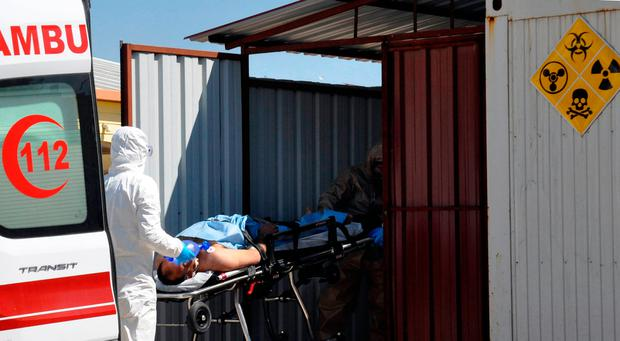 Turkish experts evacuate a victim of a suspected chemical weapons attacks in the Syrian city of Idlib, at a local hospital in Reyhanli, Turkey (DHA-Depo Photos via AP)
