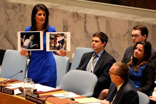 US Ambassador to the United Nations Nikki Haley holds photographs of victims during a meeting at the UN Security Council on Syria at the UN Headquarters in New York City. Photo: Reuters