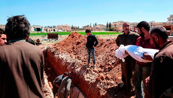 Syrians bury the bodies of victims of the suspected gas attack in the city of Idlib. Photo: AFP/Getty Images