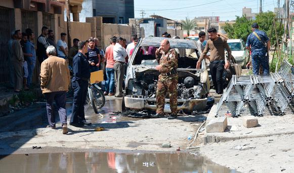 Iraqi people with security forces walk near a burnt vehicle at the site of an attack in Tikrit, Iraq. REUTERS/Stringer