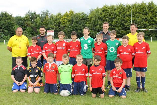 Some of the Midleton mini rugby players pictured with their coaches and Munster's Kevin O'Byrne and Denis Hurley at a summer rugby camp