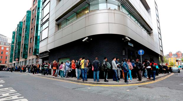 People queue at the Irish Naturalisation and Immigration service on Burgh Quay. Photo: Gerry Mooney