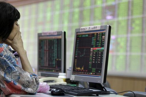 FILE PHOTO: A woman monitors stock market prices inside a brokerage in New Taipei city, Taiwan, August 24, 2015. REUTERS/Pichi Chuang/File Photo