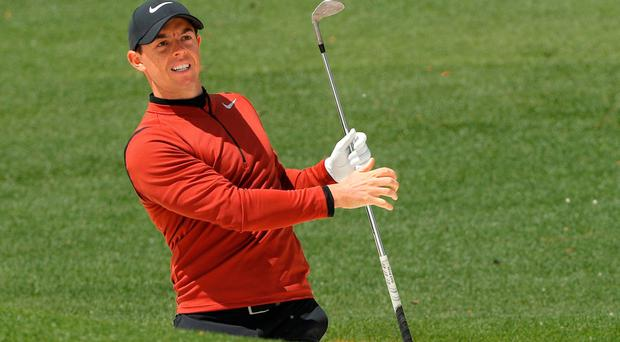 Rory McIlroy watches his shot from a bunker onto the second green