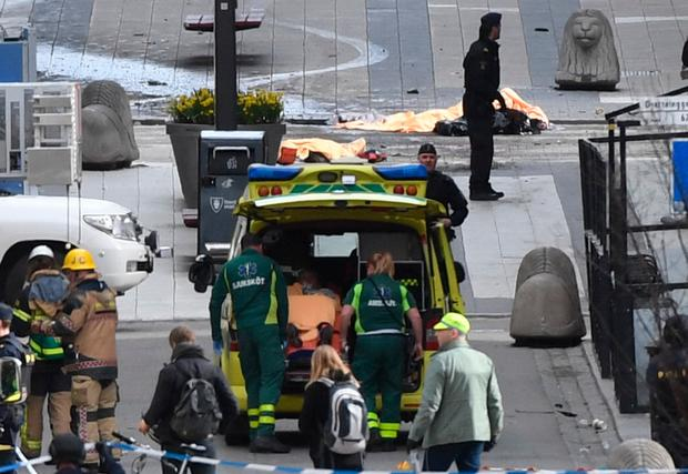 Emergency personnel load a person into an ambulance, centre, at the scene after a truck crashed into a department store injuring several people in central Stockholm, Sweden, Friday (Fredrik Sandberg/TT News Agency via AP)