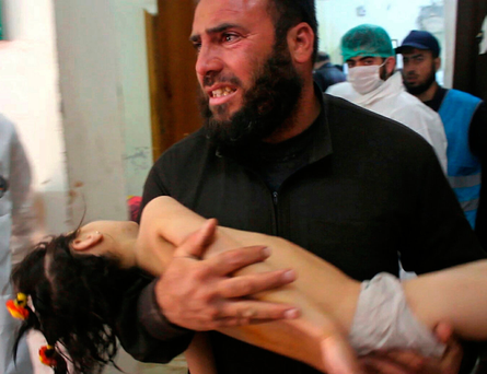 A man carrying a child at a makeshift hospital following a suspected chemical attack on Tuesday in the town of Khan Sheikhoun, northern Idlib province, Syria Photo: Edlib Media Center via AP