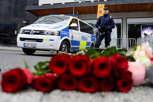 A police officer stands next to candles and flowers placed near the department store Ahlens following a suspected terror attack in central Stockholm, Sweden, Saturday, April 8, 2017. A Swedish prosecutor says a person has been formally identified as a suspect