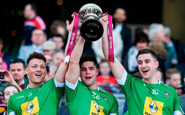 Westmeath players, from left, Tommy McDaniels, John Egan and Kelvin Reilly celebrate with the Division 4 trophy. Photo: Brendan Moran/Sportsfile