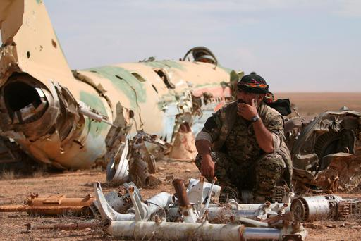 A Syrian Democratic Forces (SDF) fighter rests near destroyed airplane parts inside Tabqa military airport after taking control of it from Isil fighters, west of Raqqa city, Syria. Photo: Rodi Said/Reuters