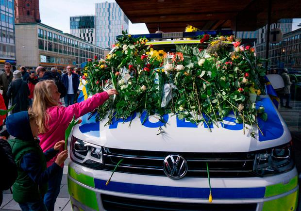 Children lay flowers at the point where a truck drove into a store in Stockholm. Photo: Jonathan Nackstrand/AFP/Getty Images