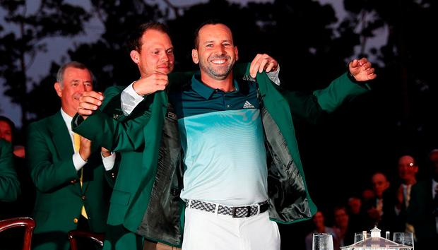 Danny Willett presents Sergio Garcia with the green jacket