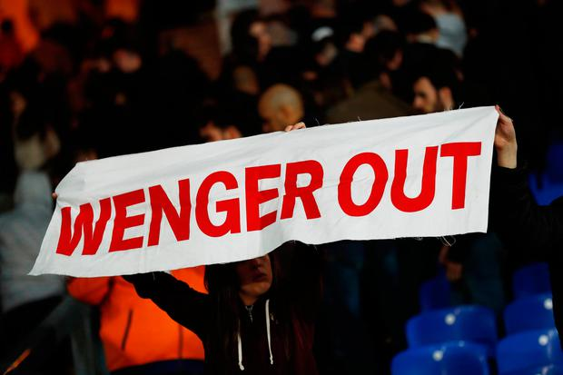 Arsenal fan holds up a message directed at manager Arsene Wenger