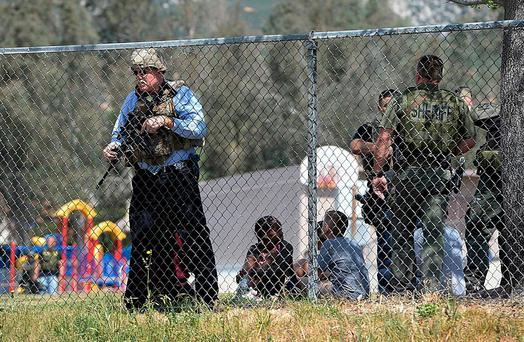 Police stand watch over students as multiple law enforcement agencies respond to a fatal shooting at North Park Elementary school in San Bernardino, California. Photo: Rick Sforza/Los Angeles Daily News via AP