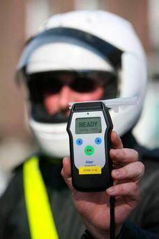 A Garda holds a breathalyser device. Stock image