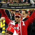 Monaco supporters with Borussia scarves react in the stadium after the match was postponed amid an explosion near the bus of Borussia Dortmund some 10km away from the stadium prior to the UEFA Champions League 1st leg quarter-final football match BVB Borussia Dortmund v Monaco in Dortmund, western Germany on April 11, 2017. / AFP PHOTO / Odd ANDERSEN