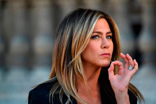 US actress Jennifer Aniston gestures as she poses during a photocall ahead of a diner for the launch of a Louis Vuitton leather goods collection in collaboration with US artist Jeff Koons, at the Louvre in Paris on April 11, 2017. / AFP PHOTO / GABRIEL BOUYSGABRIEL BOUYS/AFP/Getty Images