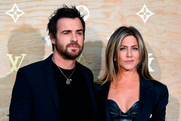 US actor Justin Theroux (L) and his wife US actress Jennifer Aniston (R) pose during a photocall ahead of a diner for the launch of a Louis Vuitton leather goods collection in collaboration with US artist Jeff Koons, at the Louvre in Paris on April 11, 2017. / AFP PHOTO / GABRIEL BOUYSGABRIEL BOUYS/AFP/Getty Images
