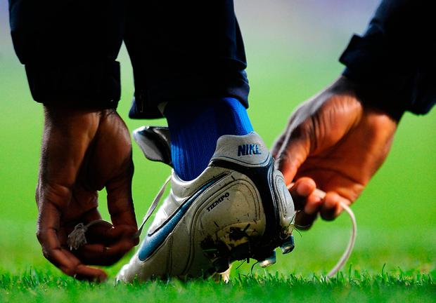 File photo of a man tying the laces on a pair of football boots. Scientists have finally solved the knotty problem of unravelling laces: Anthony Devlin/PA Wire