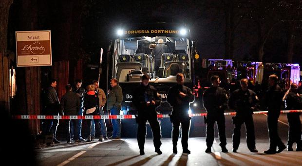 Police officers stand in front of Dortmund's damaged team bus