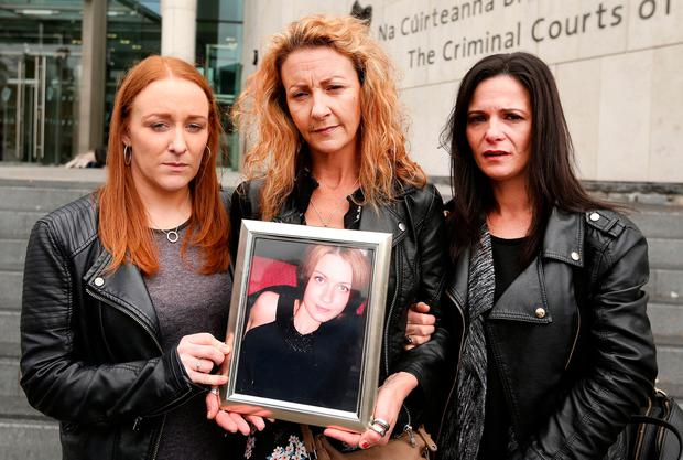 Caoimhe De Brun, Anna's sister Lisa Finnegan and Janice O'Neill hold a picture of Anna outside court