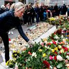 A woman lays flowers in front of the department store Ahlens in Stockholm, Sweden. Photo: AP