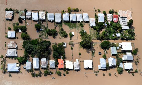 Houses are surrounded by floodwaters brought on by Cyclone Debbie at Depot Hill in Rockhampton, Australia, April 6, 2017. Photo: AAP/Dan Peled/File Photo/via Reuters