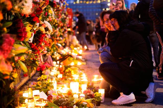Two women mourn near the Ahlens department store following last week's terror attack in Stockholm, Sweden. Photo: AP