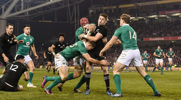 Beauden Barrett of New Zealand is driven back in the tackle by Ireland players Andrew Trimble, Garry Ringrose and Josh van der Flier during the Autumn International match between Ireland and New Zealand at the Aviva Stadium in Dublin. (Photo By Brendan Moran/Sportsfile via Getty Images)