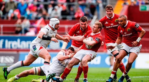 Keith Earls of Munster is tackled by Rory Best and Sean Reidy of Ulster