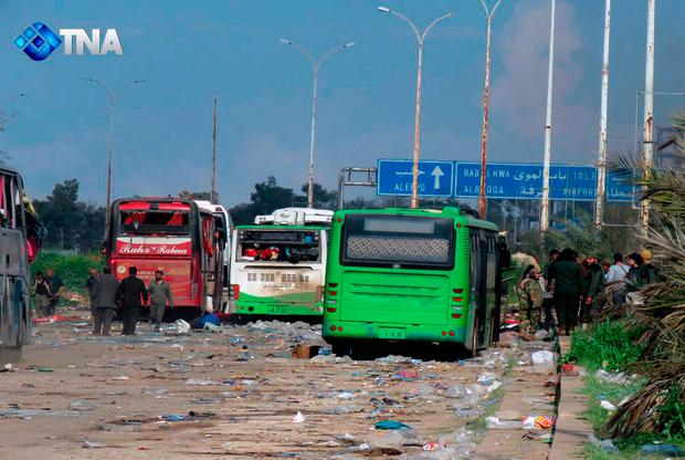 This image released by the Thiqa News Agency, shows buses at the evacuation point where an explosion hit at the Rashideen area, a rebel-controlled district outside Aleppo city, Syria (Thiqa News via AP)