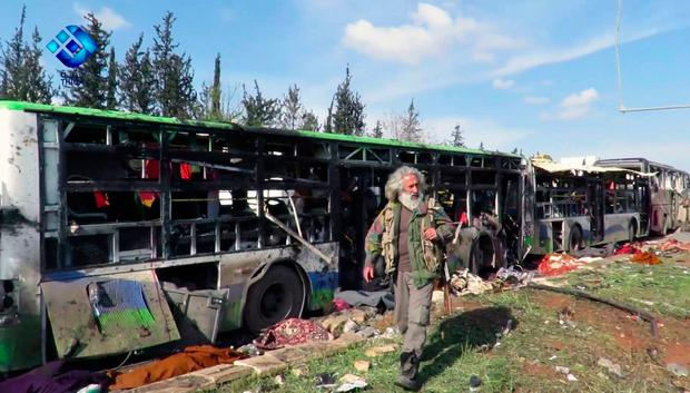 This frame grab from video provided by the Thiqa News Agency, shows a gunman passes by the buses that were damaged in a blast at the Rashideen area, a rebel-controlled district outside Aleppo city, Syria (Thiqa News via AP)