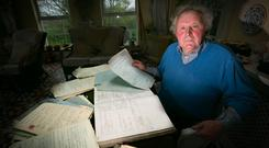 Hidden for decades: Tom Wall pictured in his home at Glin in Co Limerick with the documents from Glin Industrial School. Tom, an abuse survivor from the school, said boys from Glin were 'licensed out' to farmers as 'slaves'. Photo: Brian Gavin