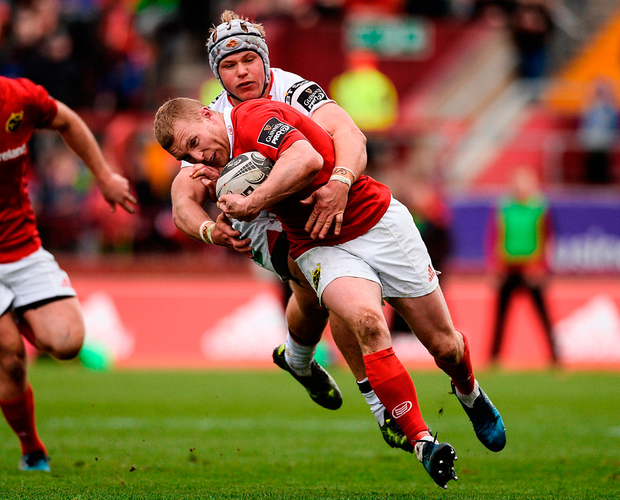 Keith Earls of Munster is tackled by Luke Marshall of Ulster Photo: Diarmuid Greene/Sportsfile