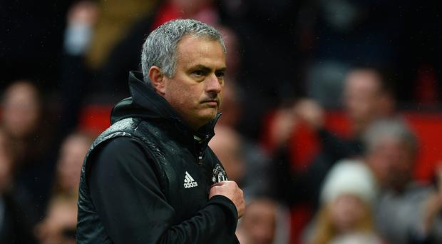 Manchester United's Portuguese manager Jose Mourinho points at the badge on his chest after his side's 2-0 win against Chelsea on Sunday