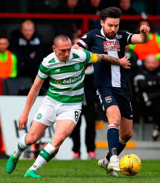 Celtic's Scott Brown and Ross County's Ryan Dow (right) struggle for posession. Photo credit: Jane Barlow/PA Wire