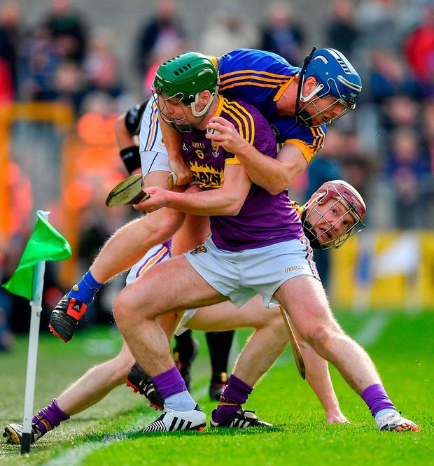 Tipp's Jason Forde is tackled by Wexford's Aidan Nolan. Photo: Ramsey Cardy/Sportsfile