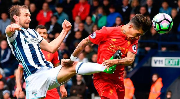 Liverpool's Roberto Firmino beats West Brom's Craig Dawson to the ball to head home the game's only goal. Photo: Getty Images