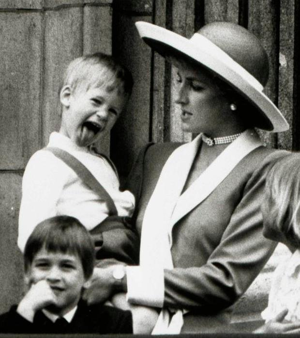 Prince Harry smiles with his mother Princess Diana while Prince William looks over a balcony at Buckingham Palace. Photo: REUTERS